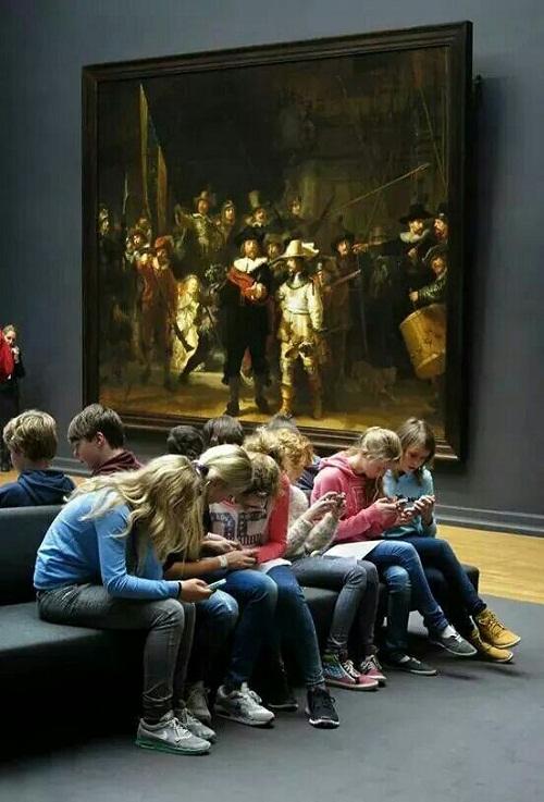 Młodzież w muzeum wpatrzona w smartfony